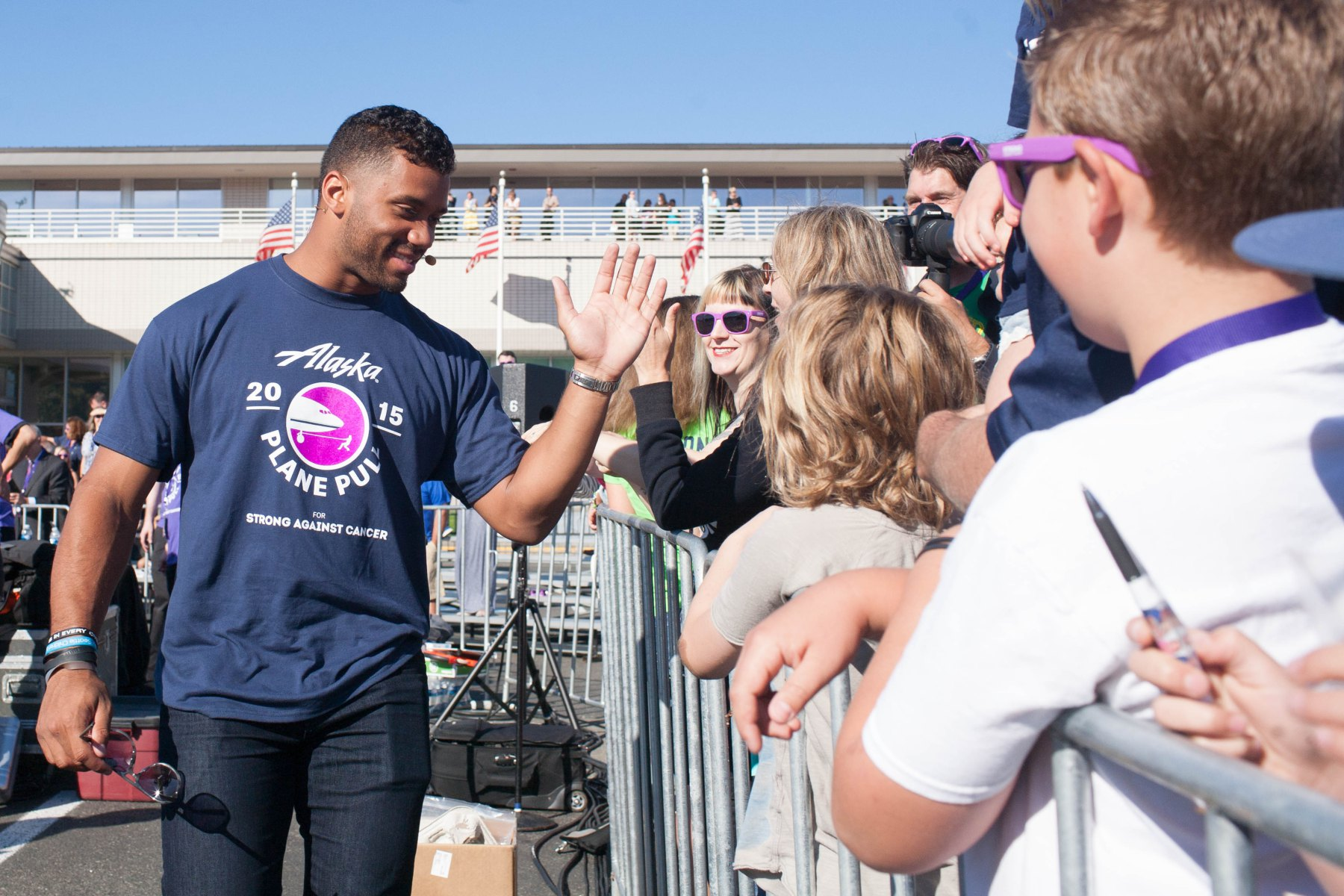 Russell Wilson gives high-fives to fans during the Alaska Airlines Plane Pull benefiting Strong Against Cancer at The Museum of Flight in Seattle on Tuesday, July 28, 2015.